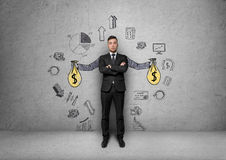 Businessman stands over background with painted hands holding money bags surrounded by economic and statistical graphs. Passive income and profits. Srategic royalty free stock photography