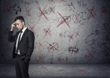 Businessman stands pondering on the concrete background with depicted ideas that crossed by red Stock Photos