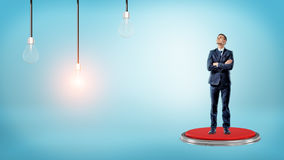 A businessman stands on a pushbutton and looks up to a glowing lamp near two others. Stock Image