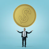 Businessman stands rising his hands towards big golden coin isolated on blue background Royalty Free Stock Photography