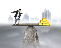 Businessman stands on rocky seesaw vs stack of gold Royalty Free Stock Image