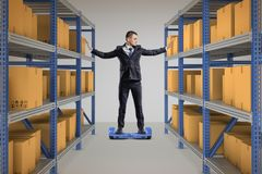 A businessman stands on a self-balancing scooter between two full storage racks. stock photography