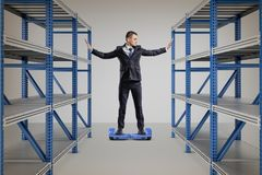 A businessman stands on a self-balancing scooter between two storage racks. royalty free stock photo
