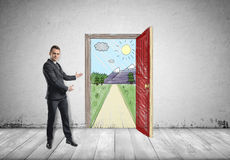 Businessman stands showing sunny scene with the road and mountains behind an open door by both hands stock photos