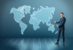 Businessman stands showing world map by both hands Stock Photos