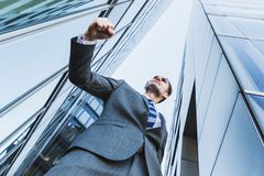 Businessman in the city makes a winners fist Royalty Free Stock Image