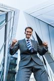 Businessman stands between skyscrapers and makes a winners fist Royalty Free Stock Photo