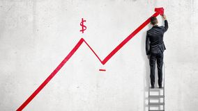 A businessman stands on a step ladder and draws a red statistic arrow moving up with a dollar sign. Business growth. Planning and strategy. Earnings and Royalty Free Stock Images