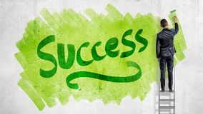 A businessman stands on a stepladder and paints a word Success on a green background with a paint roller. Business and success. Development and growth Stock Images