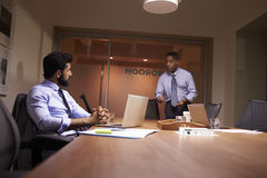 Businessman stands talking to work colleague late in office stock images