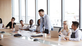 Businessman Stands To Address Meeting Around Board Table stock photos
