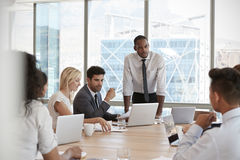 Businessman Stands To Address Meeting Around Board Table royalty free stock photos