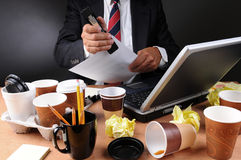 Businessman Stapling Papers at Messy Desk. Closeup view of a very cluttered businessmans desk. Man is stapling papers with coffee cups and crumpled papers litter Stock Photo
