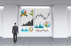 Businessman staring at graphs. Businessman in gray suit standing in front of big whiteboard with sketches of graphs on it developing new strategy for his firm Royalty Free Stock Photo