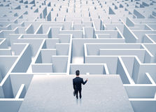 Businessman staring at infinite maze. An elegant businessman standing on a square platform looking over infinite labyrinth concept Royalty Free Stock Photography