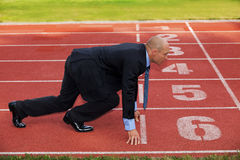 Businessman at the start line of running track Stock Photo