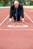 Businessman at the start line of running track Stock Image