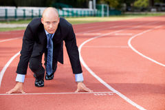 Businessman at the start line of running track Royalty Free Stock Image