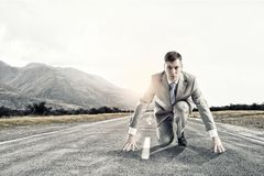 Businessman at start. Young businessman standing in start pose ready to run Royalty Free Stock Photo