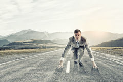 Businessman at start. Young businessman standing in start pose ready to run Stock Photos
