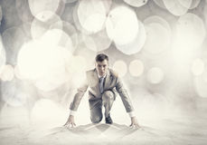 Businessman at start. Young businessman standing in start pose ready to run Stock Images