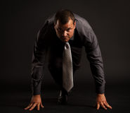 Businessman at starting position. Portrait of a competitive businessman at starting position.  on black Royalty Free Stock Image