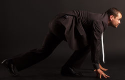 Businessman at starting position. Portrait of a competitive businessman at starting position.  on black. side view Stock Photography