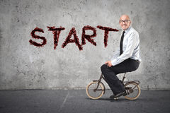 Businessman starting riding a bike Royalty Free Stock Image