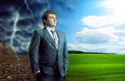Businessman staying against bad and good weather Royalty Free Stock Photo