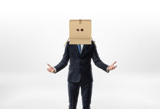 Businessman is staying his hands to the sides with a box on his head with holes for eyes on white background Royalty Free Stock Images