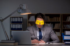 The businessman staying late to sort out priorities. Businessman staying late to sort out priorities stock photography