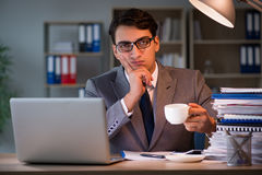 The businessman staying in the office for long hours. Businessman staying in the office for long hours stock image