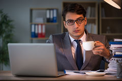 The businessman staying in the office for long hours. Businessman staying in the office for long hours Stock Photography