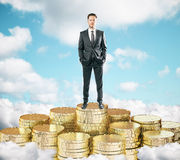 Businessman staying on pile of gold coins on the clouds t blue s Royalty Free Stock Photo