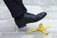 Businessman stepping on banana skin, business work accident danger concept Stock Image