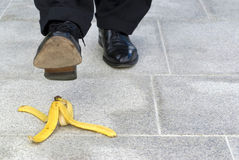 Businessman stepping on banana skin, work accident, copy space Royalty Free Stock Photo