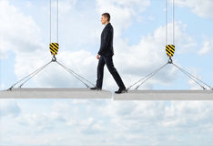 Businessman is stepping over a gap from one concrete panel to another in the air on the background of the sky Stock Image