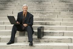 Businessman on steps. Caucasian middle aged businessman sitting on steps outdoors with laptop and briefcase smiling at viewer Stock Image