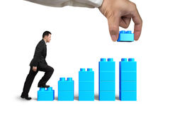 Businessman steps up bar graph stairs hand holding block complete. Businessman steps up growth bar graph shape stairs, with human hand holding a blue block to stock photos