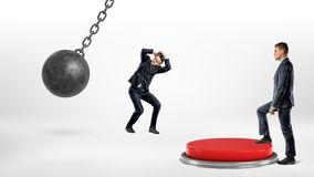 A businessman steps up on a huge floor push button to protect another man hiding from a wrecking ball. Corporate world. Business competition. Help your Royalty Free Stock Photography