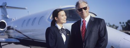 Businessman And Stewardess In Front Of An Aircraft. Portrait of senior businessman standing with beautiful stewardess in front of an aircraft Royalty Free Stock Image