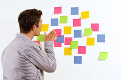 Businessman sticking sticky notes Royalty Free Stock Images
