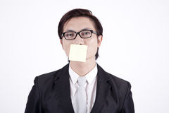 Businessman with sticky note on his mouth. Asian businessman with sticky note isolated on white Royalty Free Stock Photos