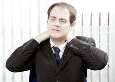 Businessman with a stiff neck. Or tension headache holding his hands behind his head while grimacing in pain Royalty Free Stock Photo