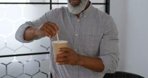 Businessman stirring coffee at office 4k. Mature businessman stirring coffee at office 4k stock video footage