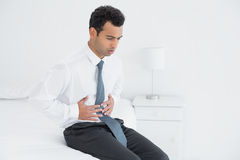 Businessman with stomach pain sitting on bed Royalty Free Stock Images
