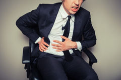 Businessman with stomach pain Royalty Free Stock Photo