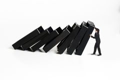 Businessman stopping the domino effect. Concept for solution to a problem by stopping the domino effect royalty free stock photos