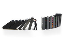 Businessman stopping the domino effect. Concept for solution to a problem by stopping the domino effect stock photos