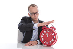 Businessman stopping time on red clock isolated on white backgro Stock Photo